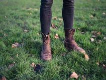 Gambe della persona che stanno sull'erba Fotografia Stock