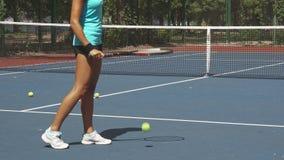 Gambe della racchetta di tennis di battitura della donna sulla palla vicino a rete sulla corte archivi video