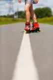 Gambe della ragazza che ha esercizio del pattino di rullo Fotografie Stock Libere da Diritti