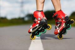 Gambe della ragazza che ha esercizio del pattino di rullo Fotografia Stock