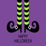 Gambe della strega con i calzini e le scarpe a strisce Halloween felice Cartolina d'auguri Progettazione piana Fondo viola del ba Fotografie Stock Libere da Diritti