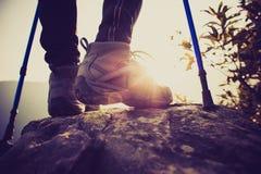 Gambe della viandante della giovane donna che scalano al picco di montagna Immagine Stock Libera da Diritti