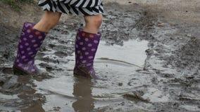 Gambe delle bambine in stivali di gomma in una pozza video d archivio