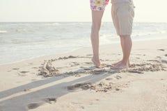 Gambe delle coppie che stanno cuore interno Immagini Stock