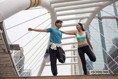 gambe di allungamento delle coppie prima dell'esercizio in città Fotografia Stock Libera da Diritti