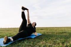 Gambe di formazione della donna di peso eccessivo sulla stuoia di yoga all'aperto immagini stock