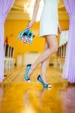 Gambe di giovane donna felice con i fiori in scarpe blu Fotografia Stock Libera da Diritti