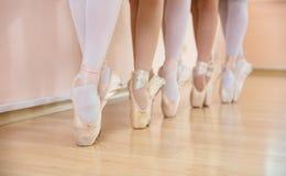 Gambe di giovani ballerine che stanno sul pointe nella fila Fotografia Stock