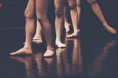 Gambe di giovani ballerine dei ballerini nel ballo classico della classe, balle fotografie stock