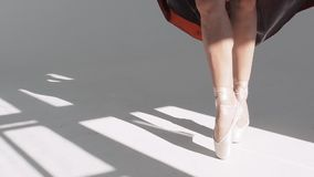 Gambe di giovani ballerini, classe di balletto Ballerino di balletto in una gonna rossa Movimento con il piede Pattini di Pointe stock footage