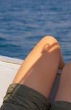 Gambe di Girs sul bordo della barca Immagini Stock
