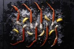Gambe di granchio fresche su ghiaccio e sul limone Fotografia Stock Libera da Diritti