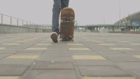 Gambe di pattinare teenager, fermantesi prendendo pattino stock footage