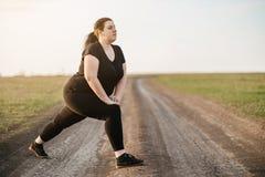 Gambe di peso eccessivo di addestramento della donna prima di pareggiare fotografie stock libere da diritti