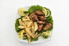 Gambe di pollo cotte con i chip Immagini Stock