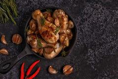 Gambe di pollo fritto con i rosmarini, l'aglio ed i peperoncini rossi Fotografie Stock