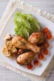 Gambe di pollo fritto con il punto di vista superiore verticale dei pomodori e dei funghi fotografia stock libera da diritti