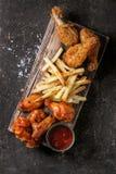 Gambe di pollo fritto con le patate fritte Immagini Stock