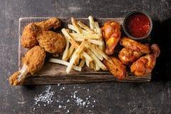 Gambe di pollo fritto con le patate fritte Fotografie Stock