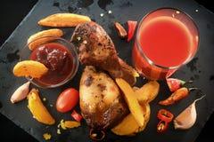 Gambe di pollo fritto con le patate, le verdure, i pomodori, il pepe, la salsa e un vetro del succo di pomodoro su un fondo nero fotografie stock libere da diritti