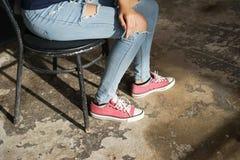 Gambe di ragazza in jeans lacerati Immagini Stock