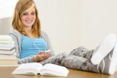 Gambe di rilassamento sorridenti dell'adolescente dello studente sulla tavola Immagini Stock