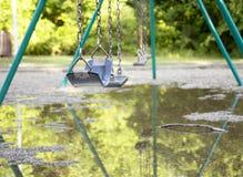 Gambe di Swingset in una pozza che riflette fuori di un'oscillazione Fotografia Stock