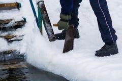 Fabbricazione di un ghiaccio-foro per l'inverno che swinning Fotografie Stock