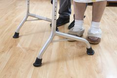 Gambe di una donna molto anziana in calzini e pantofole bianchi La signora anziana impara camminare con l'aiuto di un camminatore immagine stock