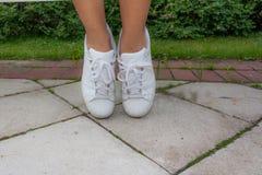 Gambe di una ragazza in scarpe da tennis bianche sulle mattonelle grige fotografia stock libera da diritti
