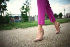 gambe di una ragazza in talloni al punto sul fondo dell'erba immagine stock libera da diritti