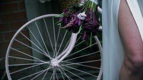 Gambe di una ragazza in un vestito bianco sui precedenti della ruota di bicicletta stock footage
