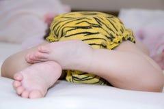 Gambe e fondo del bambino in pannolino di coloritura del leopardo a letto Fotografie Stock