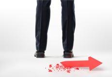 Gambe e piedi potati di un uomo d'affari con la freccia rotta rossa dietro lui su fondo bianco Fotografie Stock