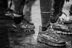 Gambe e piedi sporchi dopo avere corso sulla traccia fangosa immagine stock libera da diritti