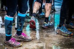 Gambe e piedi sporchi dopo avere corso sulla traccia fangosa immagine stock