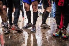 Gambe e piedi sporchi dopo avere corso sulla traccia fangosa Immagini Stock