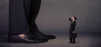 Gambe enormi con il piccolo imprenditore che sta nel concetto anteriore Immagine Stock