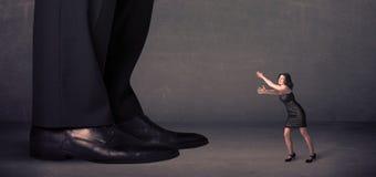 Gambe enormi con la piccola donna di affari che sta nel concetto anteriore Immagine Stock