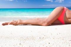 Gambe esili di Tan sulla spiaggia Fotografie Stock