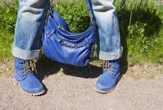 Gambe femminili in blue jeans e stivali con una borsa blu su un fondo di estate di un'erba verde Fotografia Stock Libera da Diritti