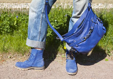 Gambe femminili in blue jeans e stivali con una borsa blu su un fondo di estate di un'erba verde Fotografia Stock