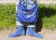 Gambe femminili in blue jeans e stivali con una borsa blu su un fondo di estate di un'erba verde Fotografie Stock Libere da Diritti