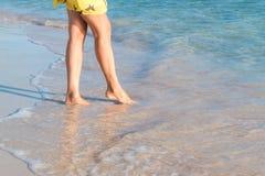 Gambe femminili che camminano sulla spiaggia Immagine Stock