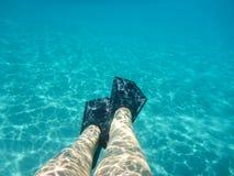 Gambe femminili con la vista subacquea delle alette di bella spiaggia di Skala dell'isola di Kefalonia, mare ionico, Grecia immagini stock libere da diritti