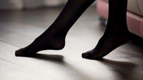 Gambe femminili eleganti in calzamaglia nere sul pavimento, sullo stile e sul modo, abbigliamento fotografia stock