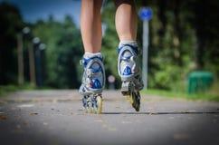 Gambe femminili in lame del rullo fotografia stock