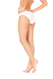 Gambe femminili in mutandine bianche del bikini fotografia stock