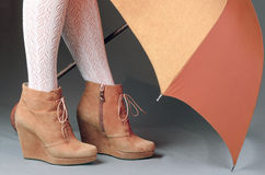 Gambe femminili negli stivali marroni della pelle scamosciata sotto un ombrello su un BAC grigio Immagini Stock