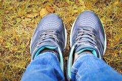 Gambe femminili nella vista delle scarpe da tennis da sopra, concetto di autunno fotografia stock